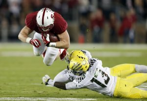 Ryan Hewitt of Stanford flies over two Oregon Ducks for a 9-yard pass reception in the second quarter at Stanford Stadium in Stanford, Calif., on Thursday, Nov. 7, 2013. (Karl Mondon/Bay Area News Group/MCT)